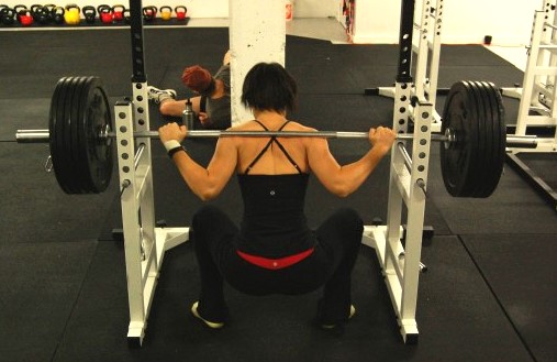 Woman squatting below parallel